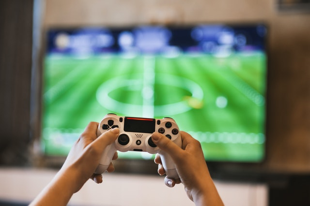 First person view of a teenager's hands on a video game controller sitting in front of screen playing a sports game