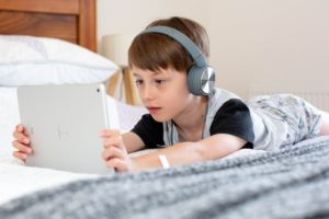 Young boy watching a tablet while wearing headphones during screentime