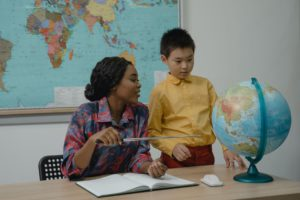 Teacher and student in classroom looking at a globe